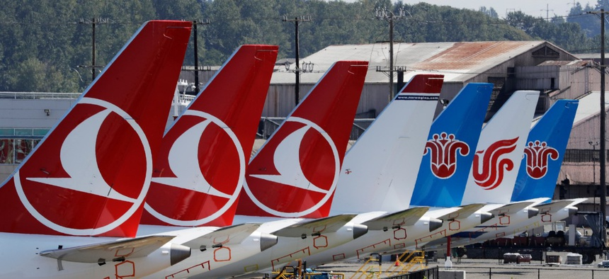 The tails of several of the dozens of grounded Boeing 737 MAX airplanes line the edge of a parking area adjacent to Boeing Field Aug. 15 in Seattle.