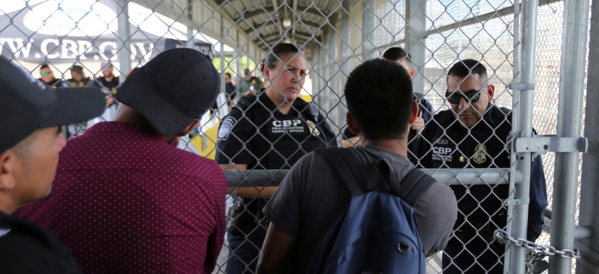 Migrants ask Customs and Border Protection officers when will the border re-open, after camping out on the Gateway International Bridge that connects downtown Matamoros, Mexico with Brownsville Oct. 10.