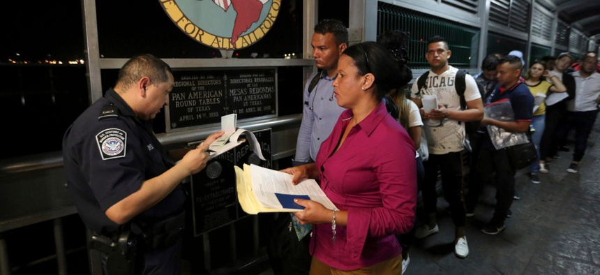 A Customs and Border Protection officer checks the documents of migrants who are on their way to apply for asylum in the United States as they depart Nuevo Laredo, Mexico, in September.
