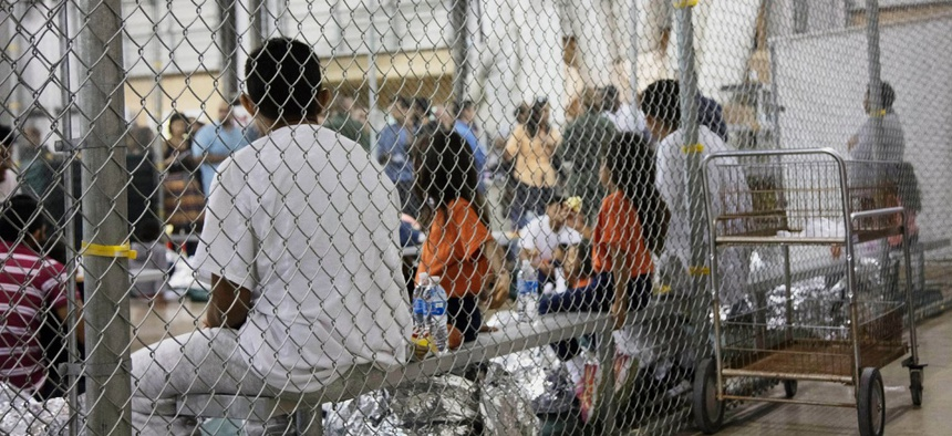 In this June 17, 2018 file photo provided by Customs and Border Protection, people who've been taken into custody related to cases of illegal entry into the United States sit in a facility in McAllen, Texas.