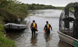 This July 2, 2019 photo provided by the U.S. Customs and Border Protection Agency shows a U.S. Border Patrol Del Rio Sector Dive Team searching for a 2-year-old Haitian girl in Rio Grande River in Del Rio, Texas.