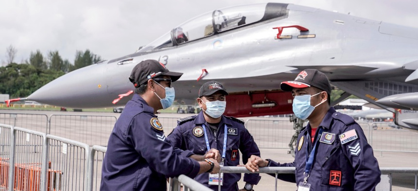 The Royal Malaysian Air Force personnel wear masks at the Static Aircraft Display area at the Singapore Airshow in Singapore Tuesday, Feb. 11, 2020 in Singapore.