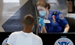 TSA officers wear protective masks at a security screening area at Seattle-Tacoma International Airport in SeaTac, Wash.