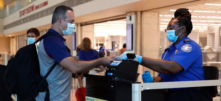 TSA agent Patrisa Johnson, right, assist travelers as they clear security for flights out of Love Field in Dallas, Wednesday, June 24, 2020.