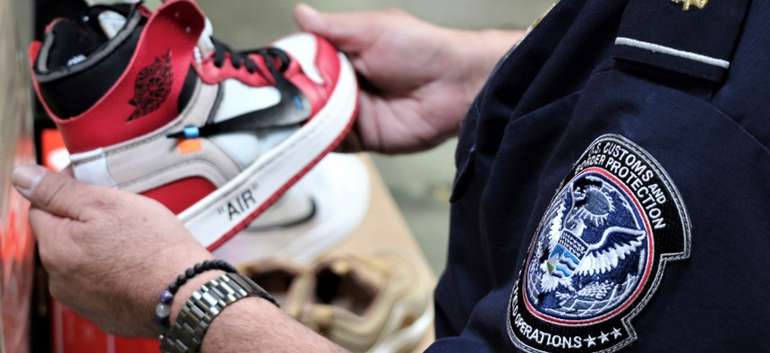 A CBP agent holds one of more than 14,800 pair of counterfeit Nike shoes, seized in a shipment arriving from China at the Los Angeles-Long Beach sports complex in 2019.