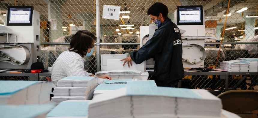 Workers use an electronic scanner as they process stacks of ballots at a Board of Elections facility, Wednesday, July 22, 2020, in New York.