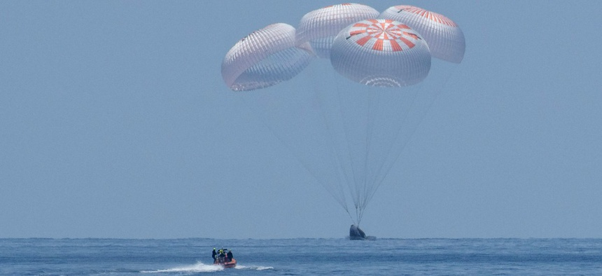 The SpaceX Crew Dragon Endeavour spacecraft lands with NASA astronauts Robert Behnken and Douglas Hurley onboard in the Gulf of Mexico off the coast of Pensacola, Fla., Aug. 2.