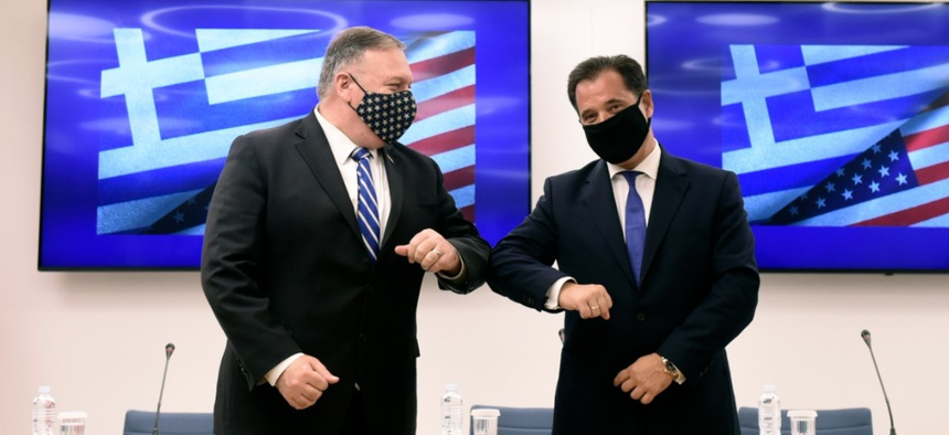 U.S. Secretary of State Mike Pompeo, left, and Greek Minister for Development and Investment Adonis Georgiadis touch elbows during a signing agreement ceremony in the northern city of Thessaloniki, Greece, Sept. 28.