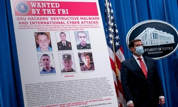A poster showing six wanted Russian military intelligence officers is displayed as Justice Department officials brief on the press on new indictments Oct. 19.