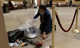 Rep. Andy Kim, D-N.J., cleans up debris and personal belongings strewn across the floor of the Rotunda in the early morning hours of Thursday, Jan. 7, 2021, after protesters stormed the Capitol.