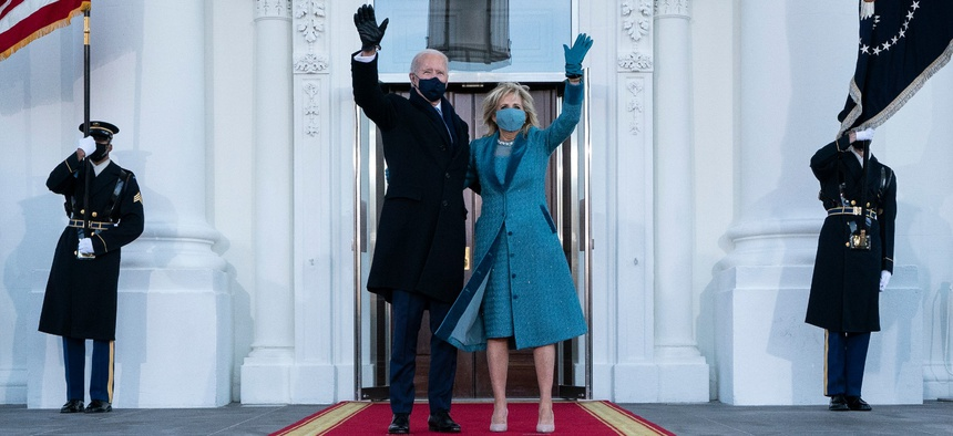 President Joe Biden and first lady Jill Biden wave as they arrive at the North Portico of the White House Jan. 20.