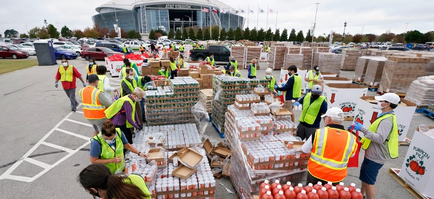 Volunteers build bags of dry goods in a parking lot outside of AT&T Stadium during a Tarrant Area Food Bank mobile pantry distribution event in Arlington, Texas in November.