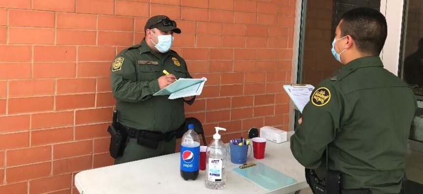 Customs and Border Protection Officer Perez checks in CBP Officer Flores at a Laredo, Texas, vaccination event.